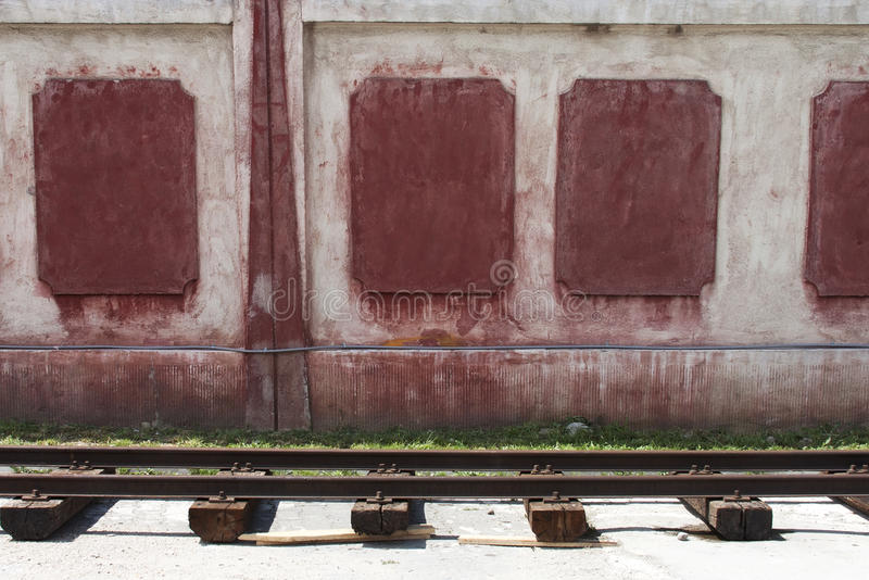 Rails and wall. Old railway rails near a red wall stock photography