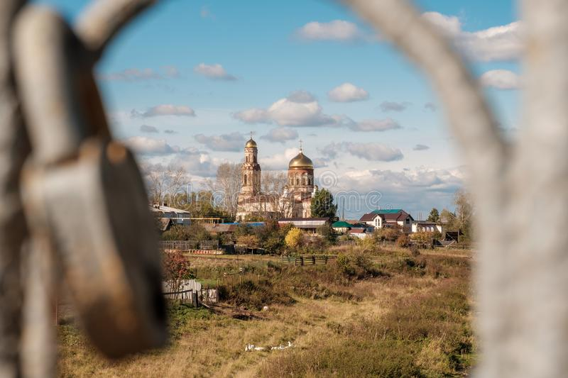Between the rails, which are suspended castle you can see the Church in the countryside. A blue sky with clouds in the autumn, Russia Ural royalty free stock images