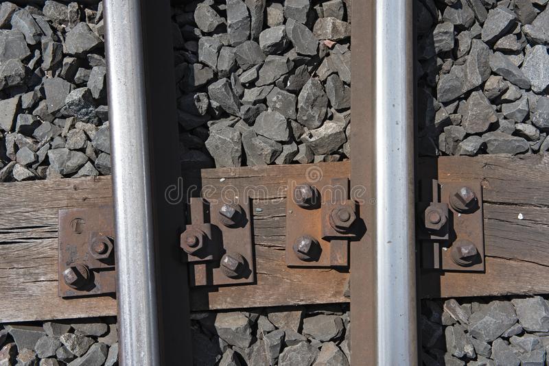 Rails on the wooden sleepers with basalt stone as a substructure.  stock photos