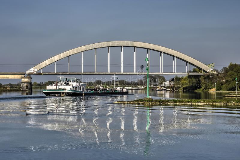 Railway bridge at Culemborg. Inland barge passing under the railway bridge accross the river Lek in Culemborg, the Netherlands stock images