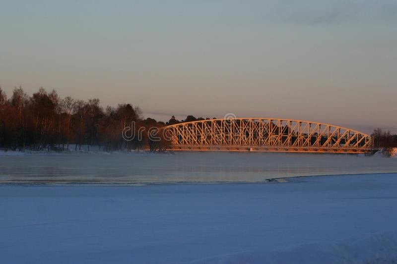 A railway bridge in evening sun on a winter day royalty free stock image
