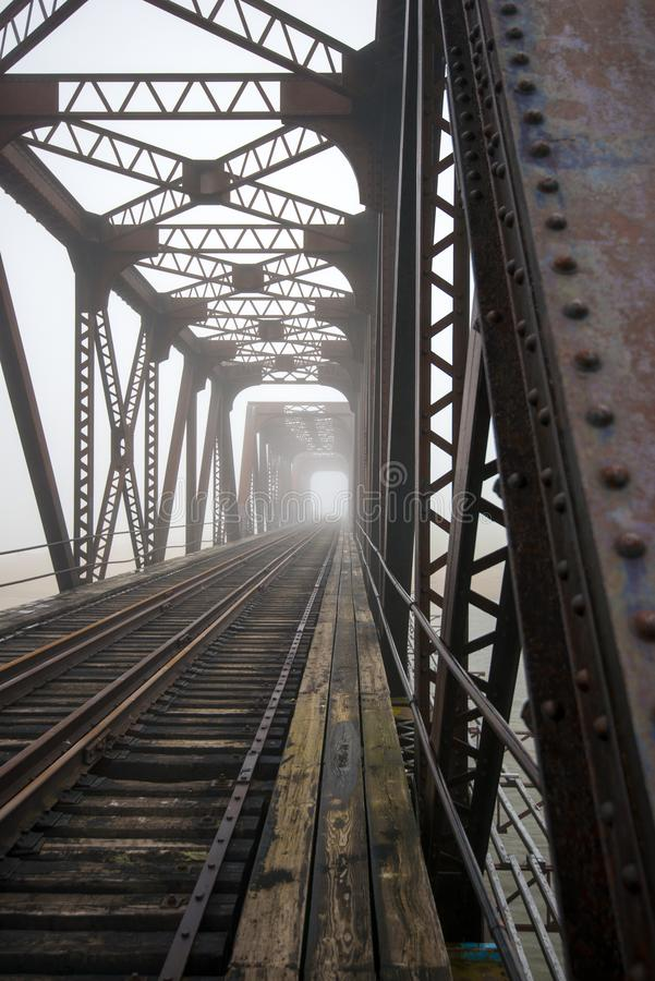 Railway bridge in fog. A perspective view of a railway bridge in the fog stock photos