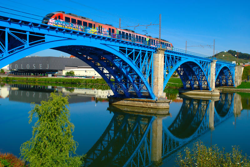 Railway Bridge, Maribor, Slovenia. Train driving across blue painted railway bridge across Drava River in Maribor, Slovenia royalty free stock image