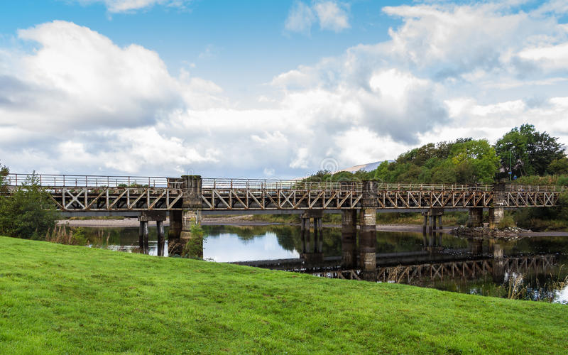 Railway bridge over river Lochy in Fort William, Scotland. Railway beam bridge crossing River Lochy on stone piers at Old Inverlochy Castle in Fort William stock photography