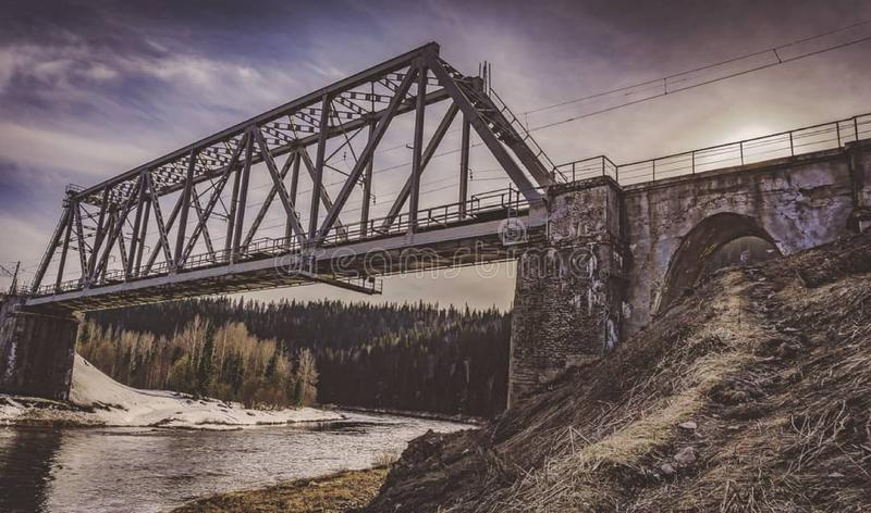 Railway bridge in the Ural mountains. Russia, color, sunset, evening, sunrise, clouds, sky, architecture, road, spring, trees, forest, nature, river, water royalty free stock photo