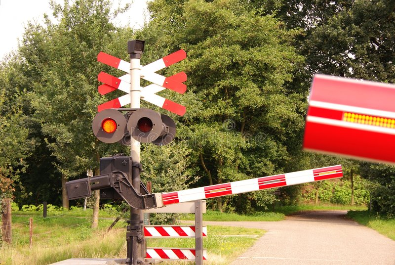 A railway crossing. The gates of a railway crossing are closing royalty free stock photo