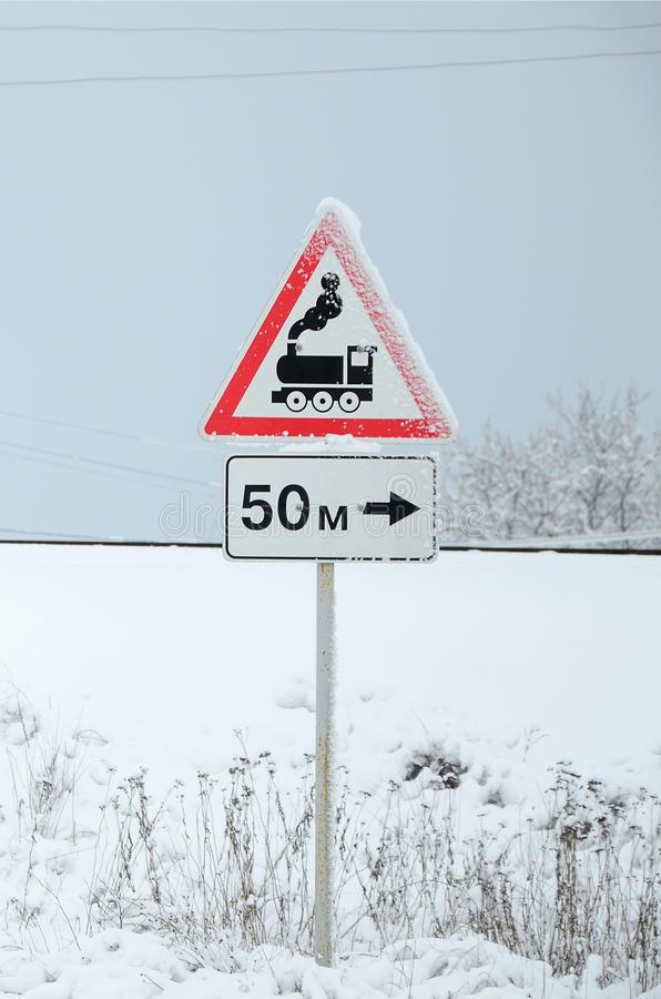 Railway crossing without barrier. A road sign depicting an old black locomotive, located in a red triangle stock photography
