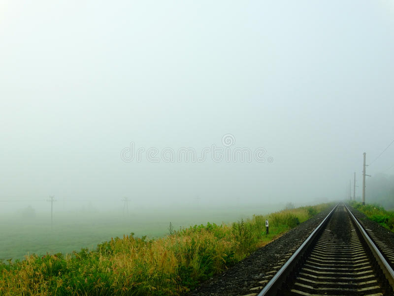 Railway in fog. Nature rails sleepers field meadow summer climate morning grass scope Russia stock photo