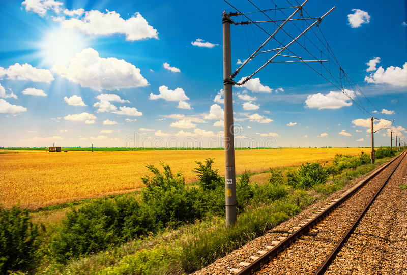 Railway Goes To Horizon In Green And Yellow Landscape Under Blue Sky With White Clouds Stock Photos