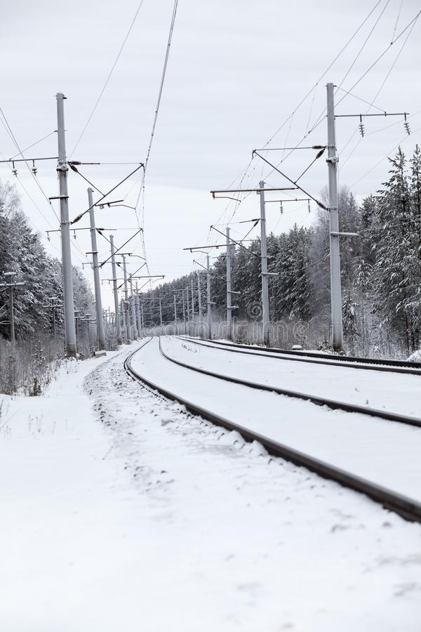 Railway line and rails on winter cold cloudy day, electric poles with wires stock photo