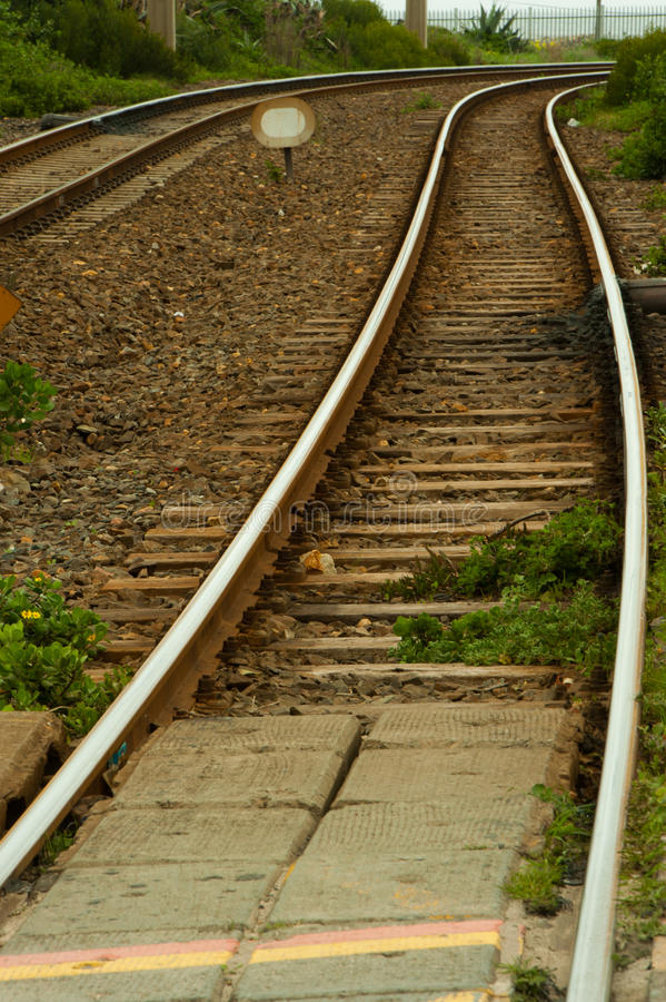Railway lines disappear around a bend. Railroad tracks turning a corner royalty free stock photography