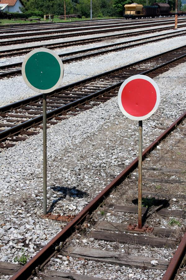 Railway lollipop like signs in green-white and red-white colors mounted on rusted metal poles. Between railway tracks and on old abandoned tracks surrounded stock photos