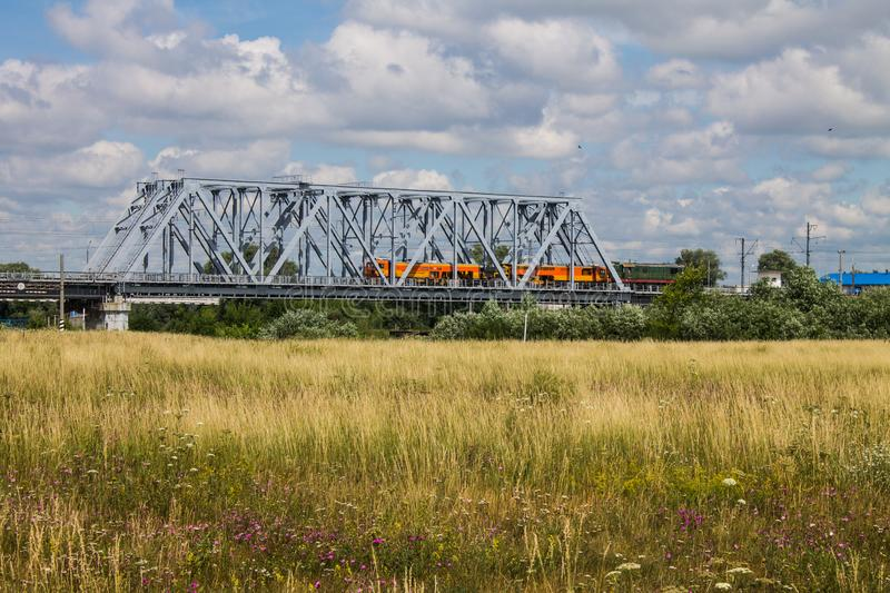 Railway metal bridge and summer meadow with high grass royalty free stock image