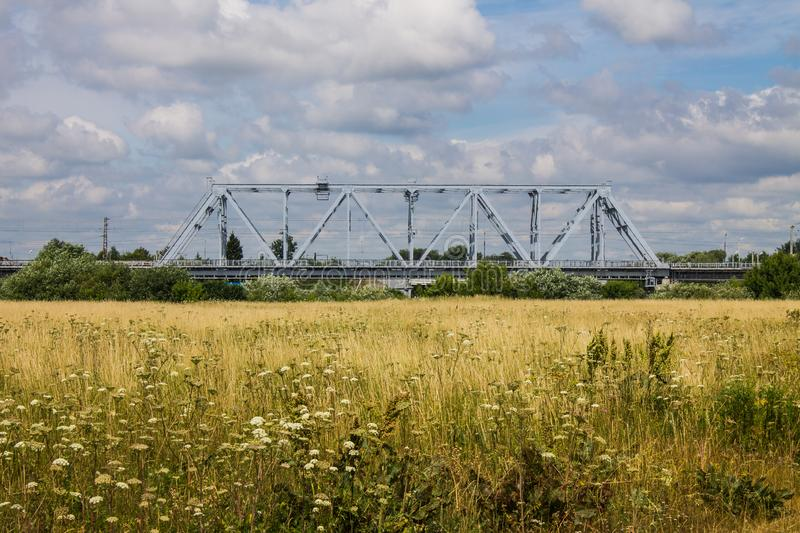 Railway metal bridge and summer meadow with high grass stock photos