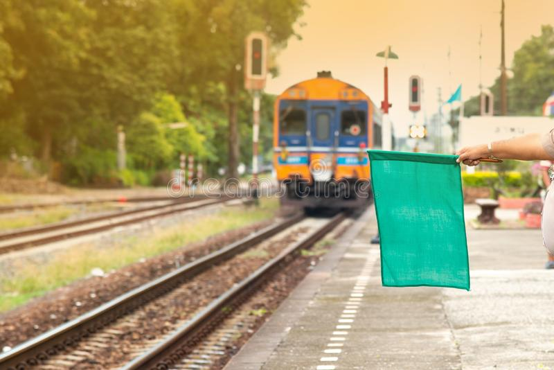 Railway officials raise the flag to display the symbol as safe. After the train leaves the station stock photo