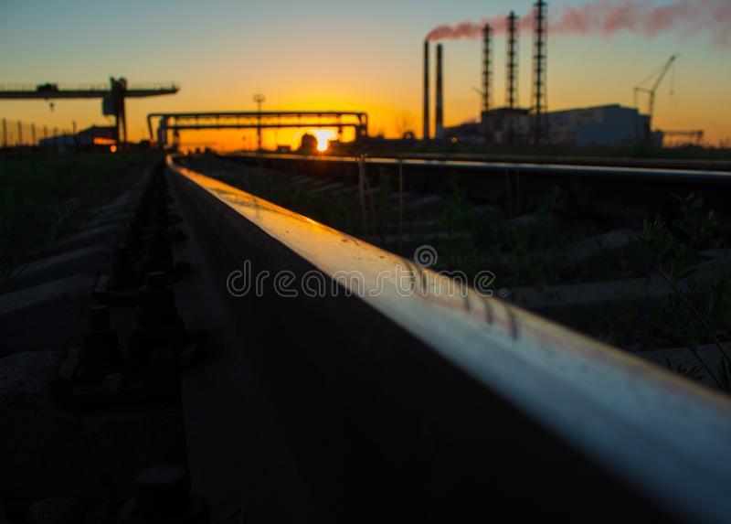 Railway. Plant. Factory. Beautiful sunset. Plant near railway at a time of sunset. Railway ties and tracks. Transportation and industries stock photography