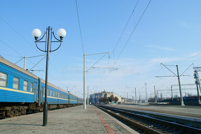 Railway platform with lamppost and passenger carriages royalty free stock photography