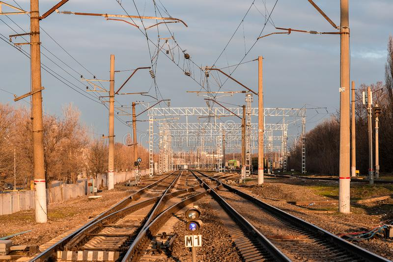 Railway rails in the evening light. Railway rails of the station in the evening in the light of the sun with a blue sky with clouds royalty free stock photos
