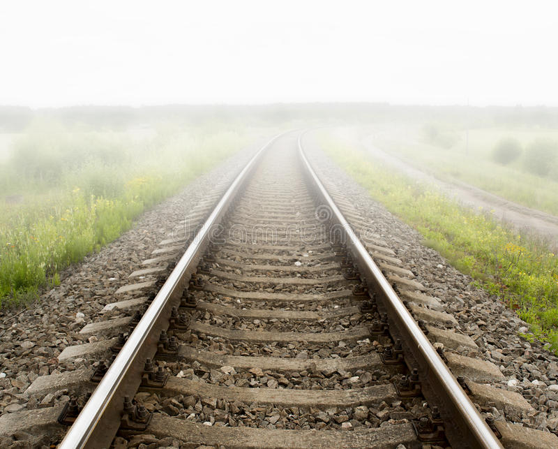 Railway rails turning to the right. Fog royalty free stock image