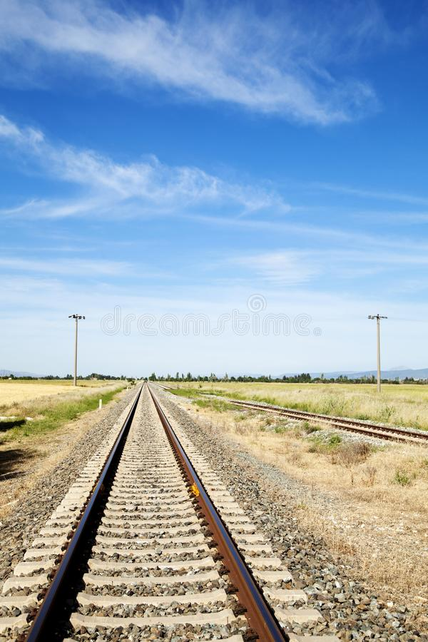 Railway station against beautiful sky at sunset. Industrial landscape with railroad, colorful blue sky with red clouds, sun, trees. And green grass. Railway stock images