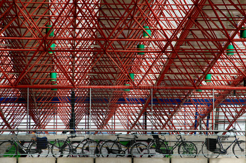 Railway station Almere. The red pipe construction of Almere's railway station in the Netherlands; bikes are parked at the platform stock image