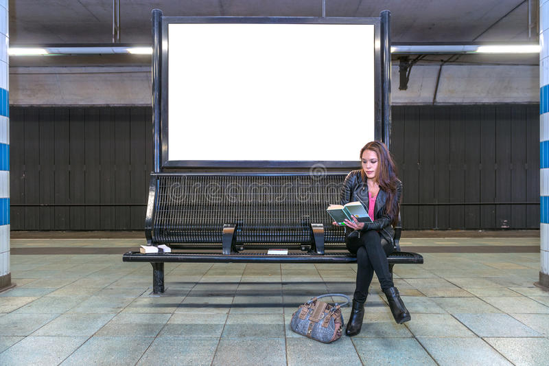 Railway station billboard and reading woman royalty free stock photography