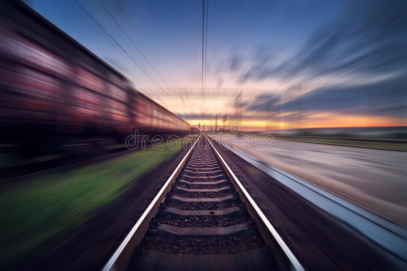Railway station with cargo wagons in motion blur effect at sunse. Railway station with cargo wagons in motion at sunset. Railroad with motion blur effect stock photo