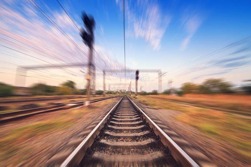 Railway station at colorful sunset with motion blur effect. Rail royalty free stock photography