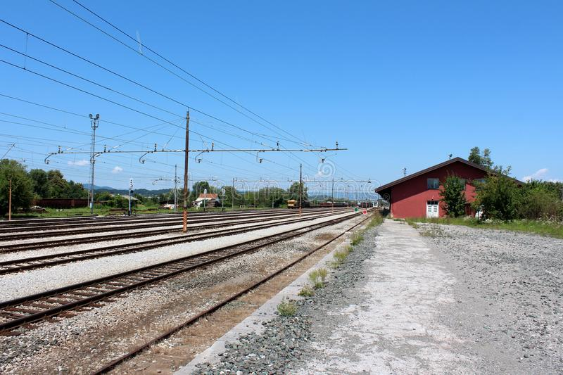 Railway station entrance with multiple railway tracks beneath electrical poles and train compositions waiting for departure royalty free stock image