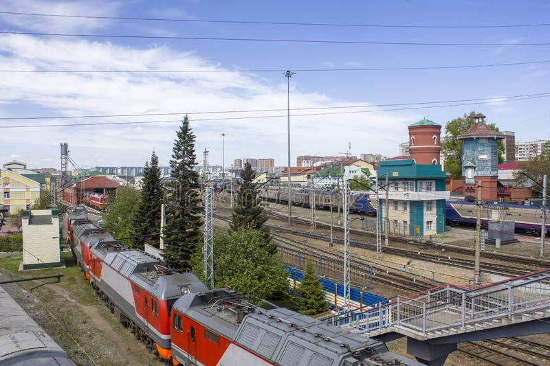 Railway station with a lot of rail tracks and the composition of the train with cars on the background of the modern city, aerial royalty free stock photography