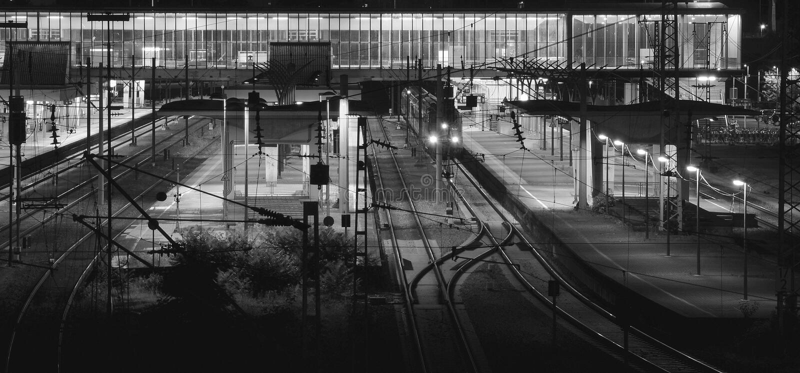Railway station at night with lonely train. A railway station in the night with a lonely train. Monochromatic image stock photos