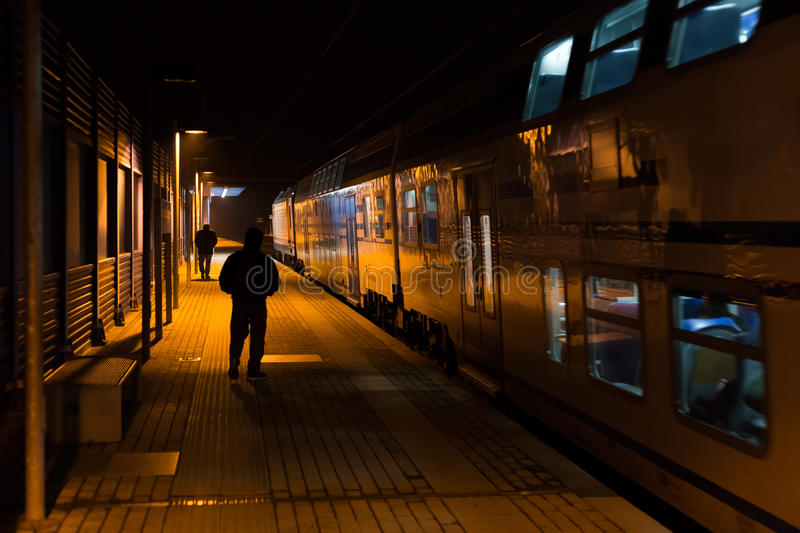 Railway station at night with train and passengers on the platform. Photo of railway station at night in Italy, Tuscany stock photography