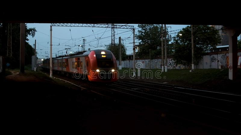 Railway station with a train passing under the road bridge in the late evening. Stock footage. View from under the stock images