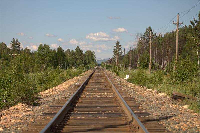 Railway to the horizon line. A railroad that goes to the horizon line in the middle of a forest. Natural beauty and transportation are combined in one image stock photos