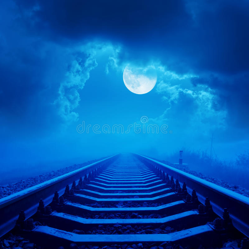 Railway to horizon in night with full moon and clouds stock images