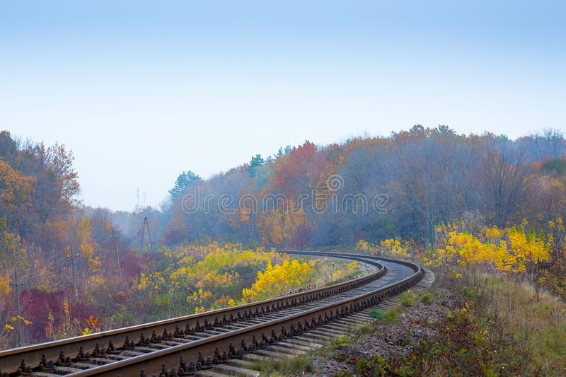 The railway track among colorful trees in the fall_. The railway track among colorful trees in the fall stock image