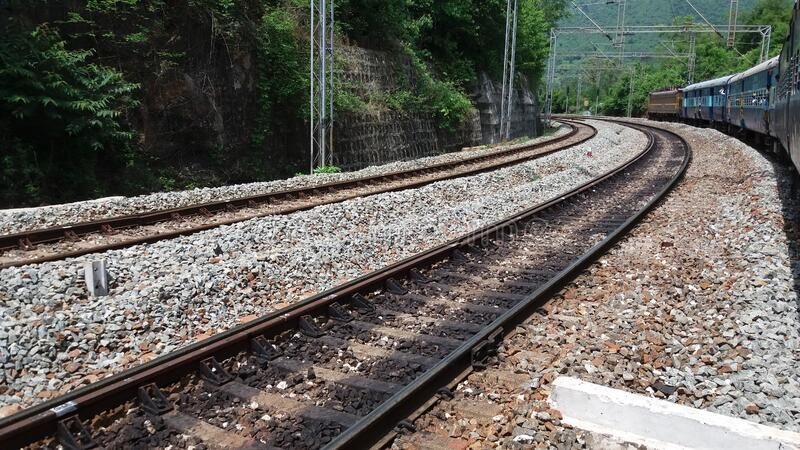 Railway track and a train taking turn on the track stock photography