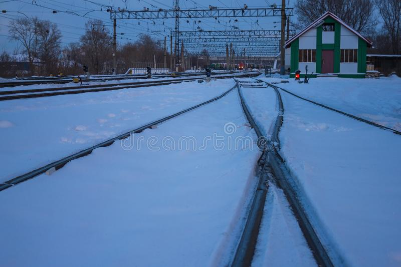 Rails at the railway station. The railway tracks are covered with snow, the rails leave into the distance. Long haul, stop. Cold winter evening royalty free stock photo