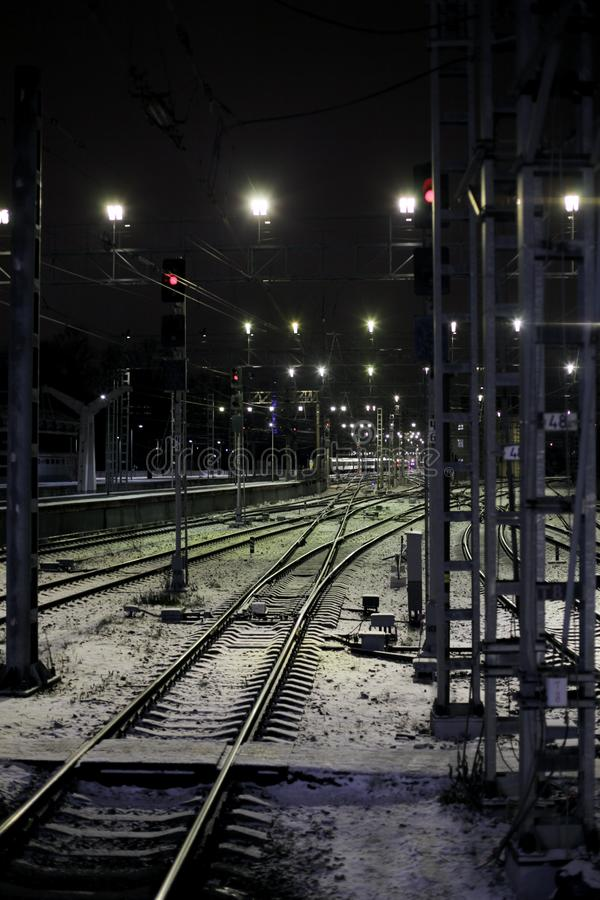 Railway tracks lit with spotlights and covered with snow during winter night 免版税库存图片