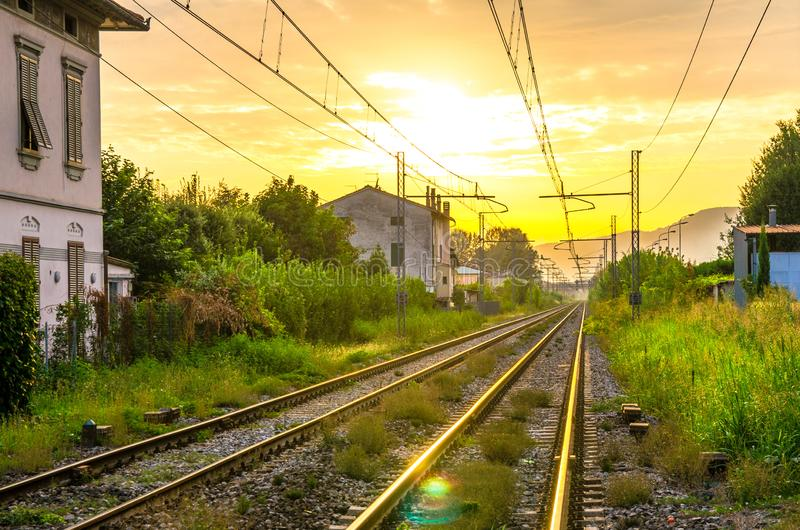 Railway tracks with old buildings on sides, wires above and Tuscany hills and mountains with dramatic cloudy yellow orange sky bac royalty free stock images