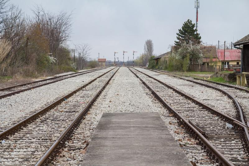 Railway tracks, rails and platforms in a rural train station in Palic, Serbia, taken during  a cold, grey and cloudy winter aftern. Picture of the train stock photo