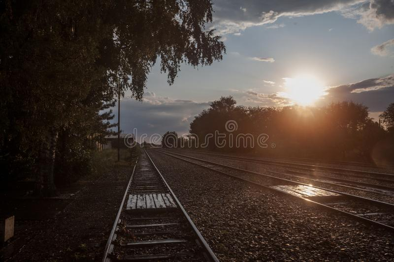 Railway tracks, rails and platforms in a rural train station in Uljma, Serbia, taken during sunset after a rain, with trees. Picture of the train station of stock images