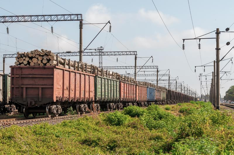 Railway tracks, wagons loaded with logs on rails stock image