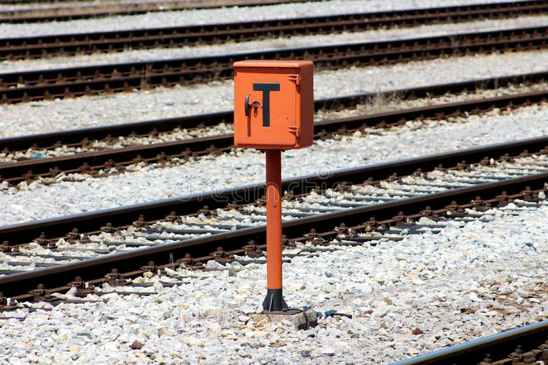 Railway trackside orange communication utility box mounted on metal pole and positioned on gravel between railway tracks. Railway trackside orange communication royalty free stock image