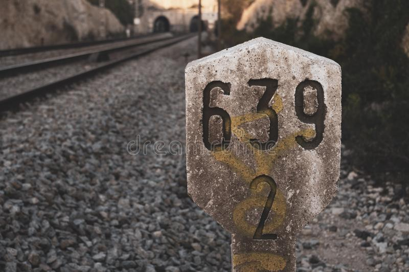 Railway traffic sign next to train tracks with kilometric numbering in concrete marker. Two tunnels, vintage atmosphere stock photography
