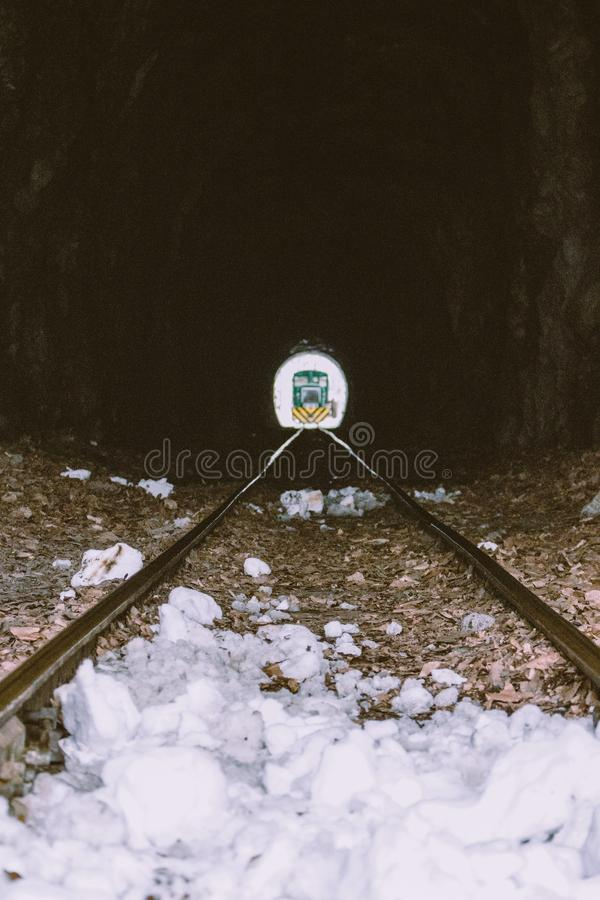 Railway tunnel with train at the end. Green locomotive at the end of tunnel. Transportation and travel concept. Railway tunnel with train at the end. Green royalty free stock image