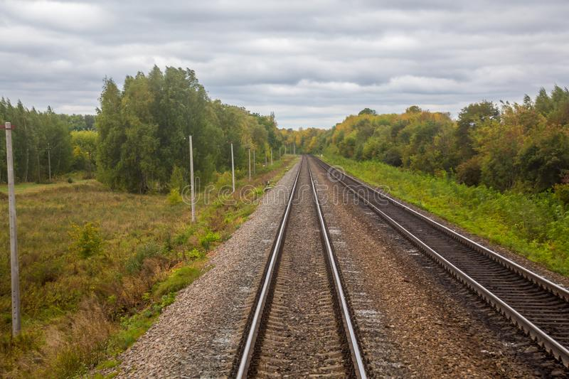 Railway. View from the window of the last train car or from the cab. Russian autumn landscape. Railway rails and sleepers stock photo