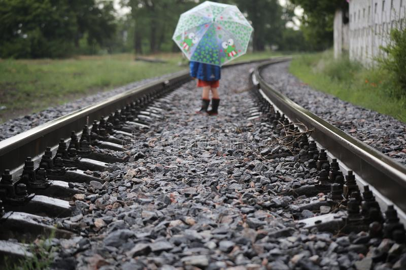Railway which goes into the distance. Open space. Rainy day. The railway that goes into the distance. Open space. Rainy day, wet iron, open umbrella. little boy royalty free stock photos
