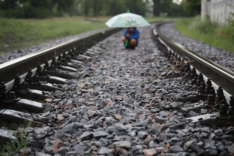Railway which goes into the distance. Open space. Rainy day. The railway that goes into the distance. Open space. Rainy day, wet iron, open umbrella. little boy stock photo