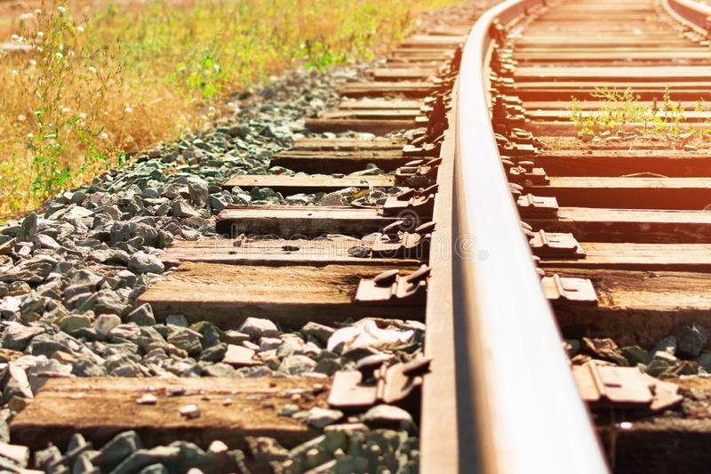 Railway wooden sleepers and rails at sunset. Railway track, wooden sleepers and metall rails, sunny picture, close up royalty free stock images